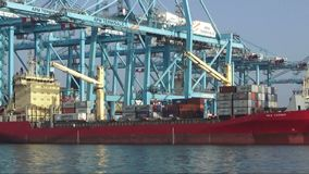 Pair of containers loaded in the containership Max Carrier. Containers special crane downloading a containership in Algeciras harbour in Cadiz stock video