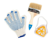 Pair of cotton gloves, paint brush and a dust mask Stock Photos