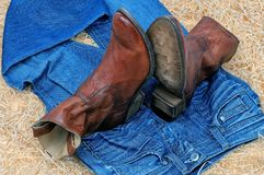 Pair of cowboy boots and blue jeans on straw royalty free stock photo