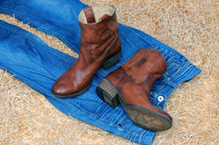 Pair of cowboy boots and blue jeans on straw royalty free stock images
