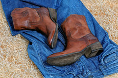 Pair of cowboy boots and blue jeans on straw royalty free stock photos