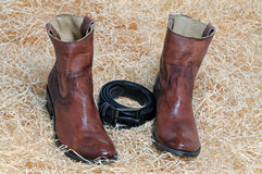 Pair of cowboy boots and leather belt on straw. Pair of traditional brown leather cowboy boots and the leather brown belt curtailed into a ring on straw royalty free stock images
