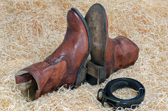 Pair of cowboy boots and leather belt on straw. Pair of traditional brown leather cowboy boots and the leather brown belt curtailed into a ring on straw royalty free stock photos