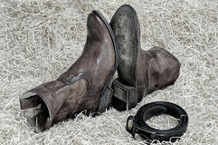 Pair of cowboy boots and leather belt on straw. Pair of traditional leather cowboy boots and the leather belt curtailed into a ring on straw. Retro and dark stock image