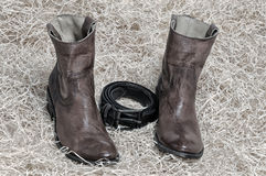 Pair of cowboy boots and leather belt on straw. Pair of traditional leather cowboy boots and the leather belt curtailed into a ring on straw. Retro and dark stock photos