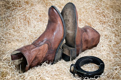 Pair of cowboy boots and leather belt on straw. Pair of traditional leather cowboy boots and the leather belt curtailed into a ring on straw. Retro toning of the stock photos