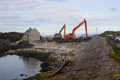 A pair of cranes used to dredge the small harbor at Ballintoy on the North Antrim Coast of Northern Ireland on a calm spring day. A pair of cranes used to royalty free stock image