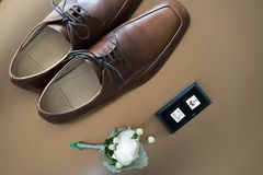 A pair of cufflinks and shoes. A pair of cuff links、shoes and flower brooch at wedding stock photo