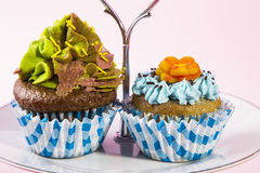 Pair of cupcakes. Decorated cupcakes on a serving plate royalty free stock photography