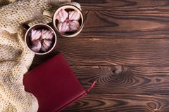 Coffee with marshmallows, woolen scarf and book on a wooden background. Winter hot chocolate. Coziness concept. stock images