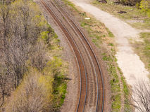 Pair of curving train tracks near forest. Stock Photo