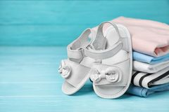 Pair of cute baby sandals and stack. Of clothes on table royalty free stock image