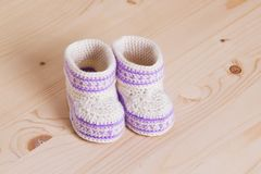 Cute Crochet baby booties  on wooden background. Pair of Cute hand made baby shoes on wooden background Stock Images