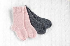 A pair of cute small different colored cashmere knitted newborn baby socks on a white woolen background stock photography