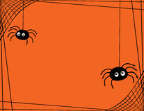 A Pair of Cute Spiders Spinning a Web Border. Two cartoon spiders hanging from a web border/frame. The the background is orange and there is room for text Stock Image