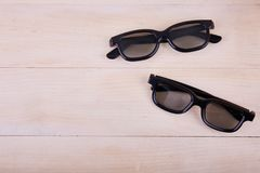 A pair of 3D glasses on the background of a wooden table royalty free stock photo