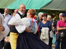 A pair of dacers in traditional folk costume. A couple dancing in traditional Swedish folk costumes at an event with a crowd of people royalty free stock image