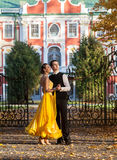 Pair of dancers dancing in the woods. Man with suit, woman in yellow long dress  middle of the palace park in autumn. Dry fallen c Stock Photo