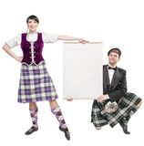 Pair of dancers of Scottish dance with empty banner Royalty Free Stock Images