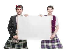 Pair of dancers of Scottish dance with empty banner Royalty Free Stock Photo