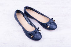 Pair of dark blue ladies` flat shoes on white wooden background.  stock image