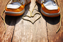 A pair of deck shoes on a nice wooden porch with the laces in a heart shape Stock Photo