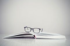 Glasses on book. A pair of designer glasses on an opened coffe table book Stock Photography