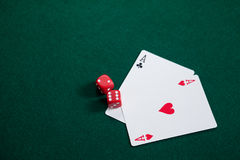 Pair of dice and playing cards on poker table Royalty Free Stock Image