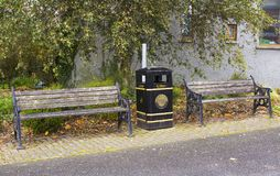 A pair of dilapidated park benches and a city council litter bin on the roadside in the small mill village of Edenderry in South B. A pair of dilapidated park Stock Image