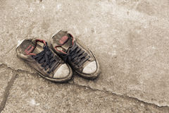 Pair of dirty black sneakers on street. Background Royalty Free Stock Image
