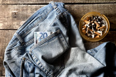 Pair of dirty jeans,twenty euro bill and an ashtray Stock Image