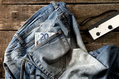 Pair of dirty jeans, twenty euro bill and vintage camera Stock Image