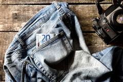 Pair of dirty jeans, twenty euro bill and vintage camera Stock Images