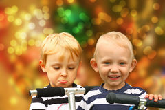Pair of disappointed and happy blond boys Royalty Free Stock Images