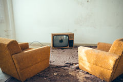 Pair of disused sofa chairs in front of broken TV Stock Photos