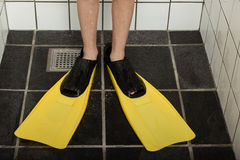Pair of diving flippers on feet in shower stall Stock Images