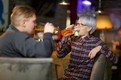 A pair are drinking beer in a bar. Indoors in a public place. royalty free stock photography