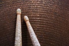 Pair of drumsticks lying on cymbal. Royalty Free Stock Photos