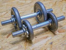 A pair of dumbbells. Closeup image of a pair of metal dumbbells on wooden background. Exercise concept stock photo