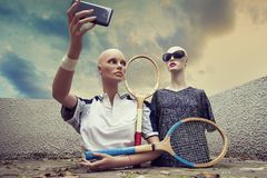 Pair of dummies take a selfie dressed in seventies tennis clothe. S and tennis racket Stock Photo