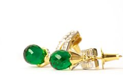 Pair of earrings  on the white background. Pair of classy gold earrings with a big Green stone Royalty Free Stock Photos