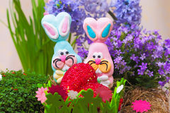 Pair of easter candy bunnies with heart. In nest Stock Images
