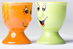 Pair of egg holders. Pair of an orange and green color ceramic egg holders with happy faces Stock Image