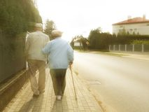 A pair of elderly people walk along the sidewalk along the road holding hands. Grandfather and grandmother on a walk in a stock photos