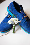 Pair of elegant grooms blue shoes with boutonniere Royalty Free Stock Photography