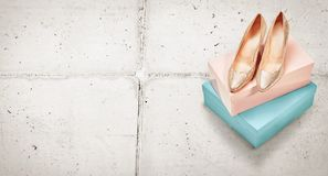 Pair of elegant metallic gold high heeled shoes. Pair of elegant metallic gold high heeled court shoes for evening wear displayed on top of two colorful boxes on royalty free stock photo