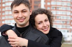 Pair embraces and smiles against building Stock Image