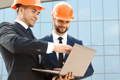 Pair of engineers examining their plans on laptop Royalty Free Stock Photos
