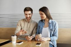Pair of enthusiastic marketing specialists sitting at table in cafe, smiling, drinking coffee, talking about work, using Stock Images