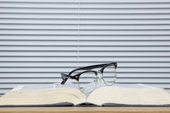 Pair of eye glasses on a worn open text book Royalty Free Stock Photos